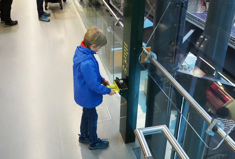 Ett barn stämplar en papperslapp i en automat.