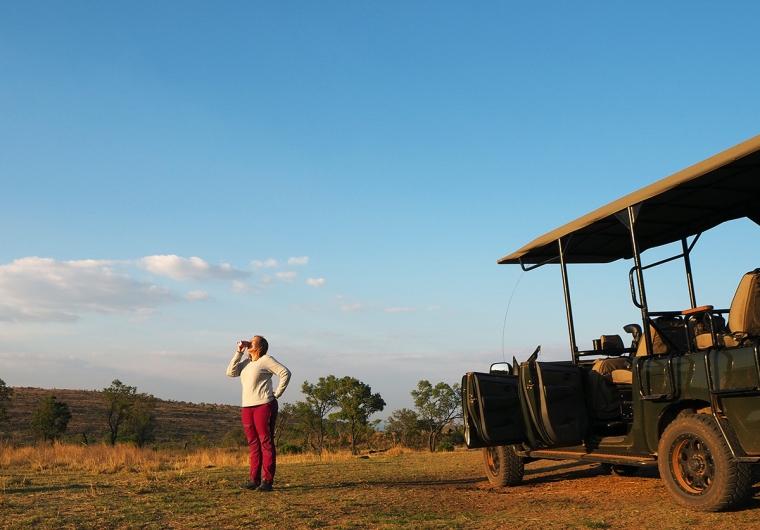 En kvinna står och halsar läsk med en savann i bakgrunden och en safarijeep i förgrunden.
