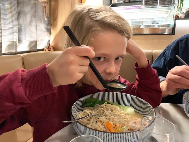 Ett barn äter ramen-soppa med stor slev.