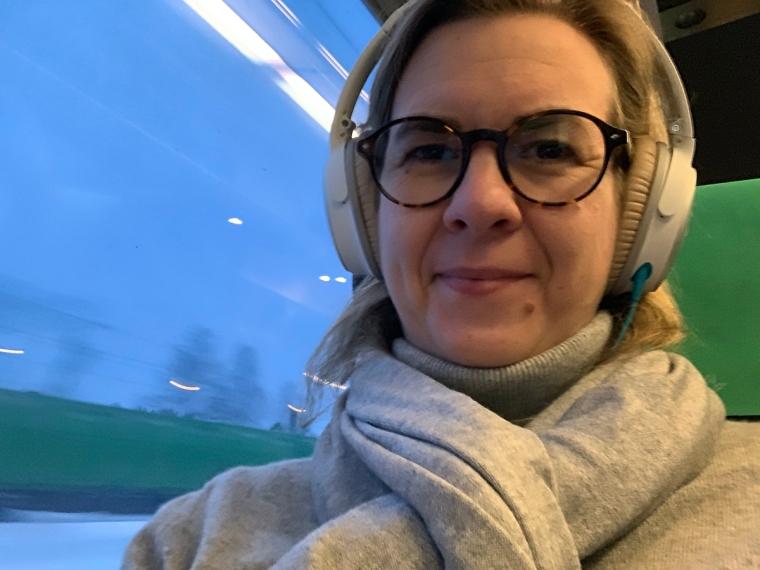Kvinna på tåg med hörlurar på-