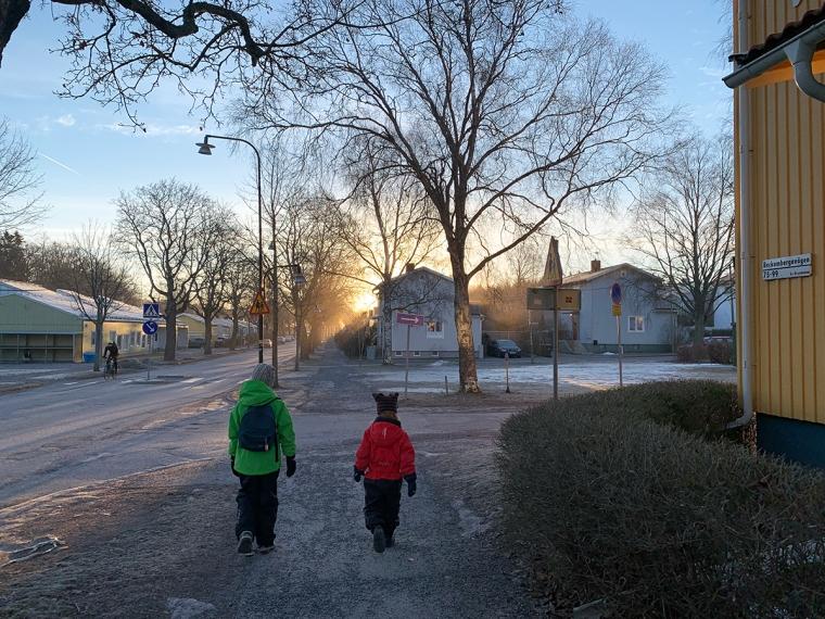 Två barn som går på en gata i motljus.