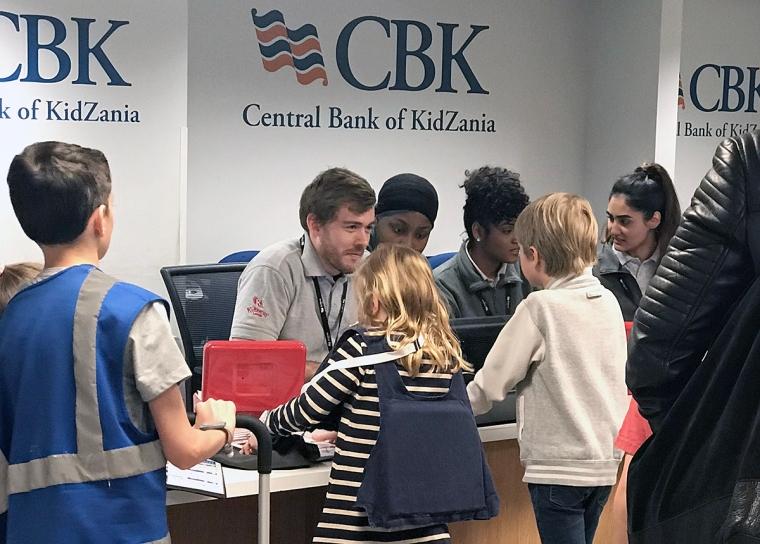 Vuxna som jobbar bakomen disk på en låtsasbank. Barn som är kunder.