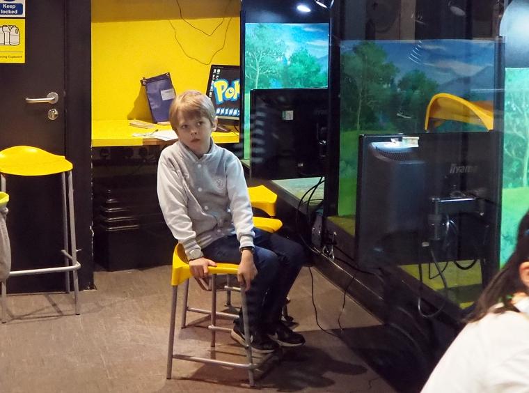 Ett barn sitter på en gul pall.