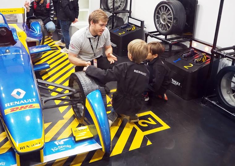 Två barn få instruktioner från en vuxen om hur de ska byta däck på en racerbil.