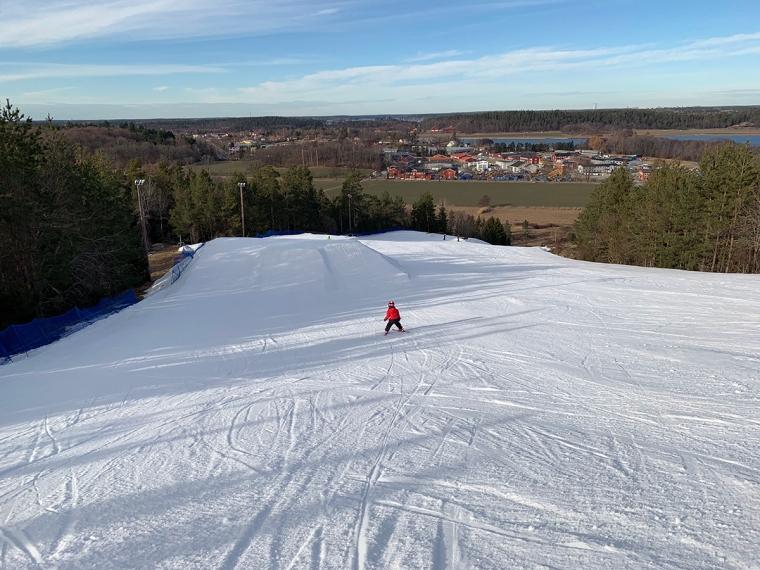 Ett barn som åker skidor i en annars tom slalombacke.