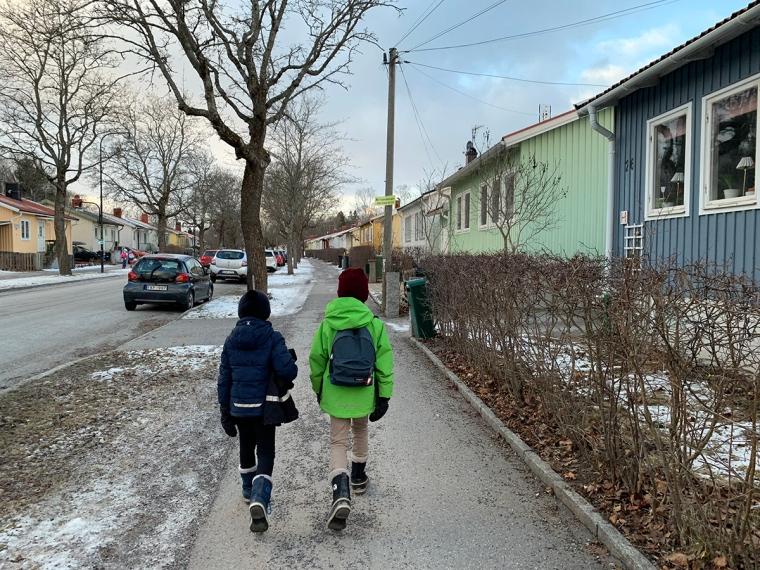 Två barn går längs en väg.