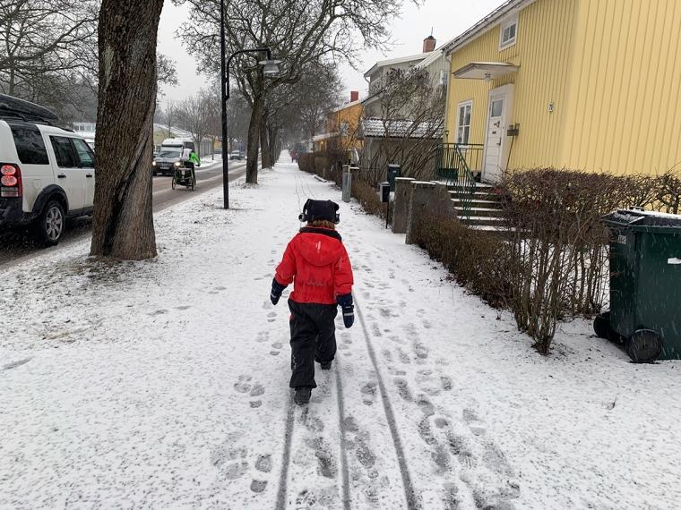 Ett barn som går på en trottoar med snö.