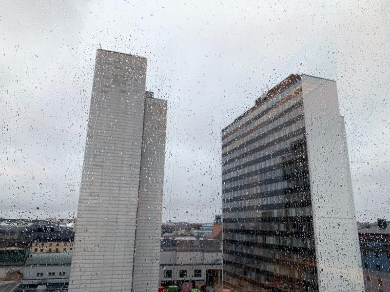 Fönster med regndroppar på. Utanför två höghus (Hötorgsskrapor).