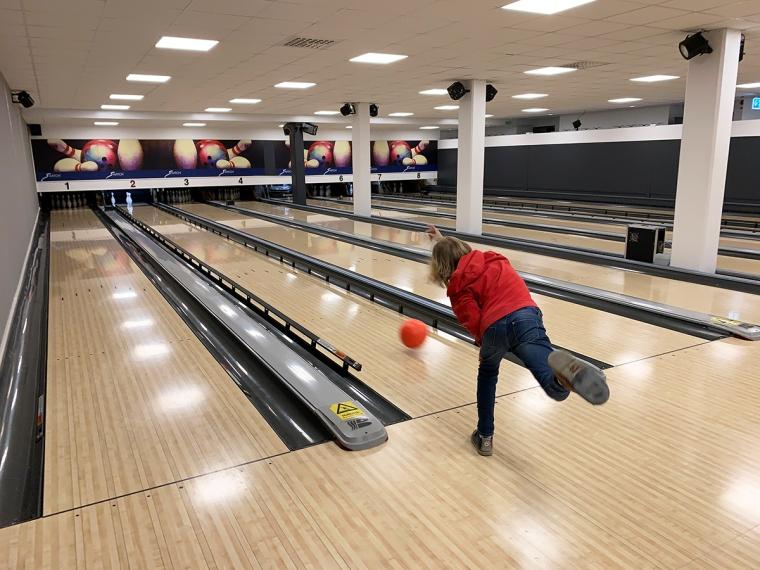 Ett barn som kastar iväg sitt bowlingsklot.