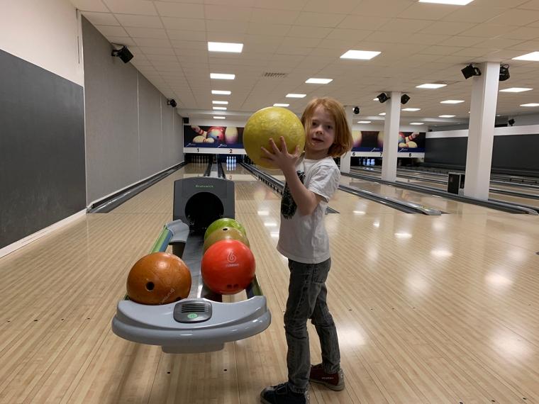 Ett barn som står med ett gult bowlingsklot i händerna.