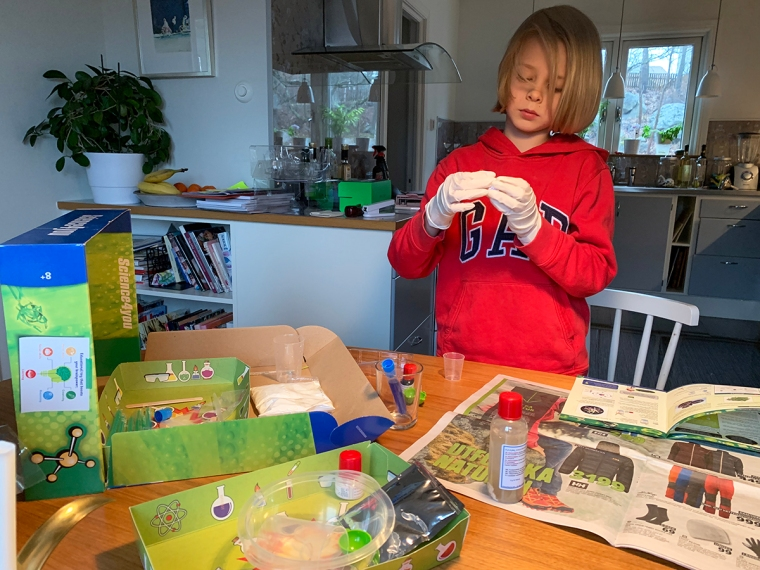 Ett barn i plasthandskar håller på med olika burkar och flaskor.