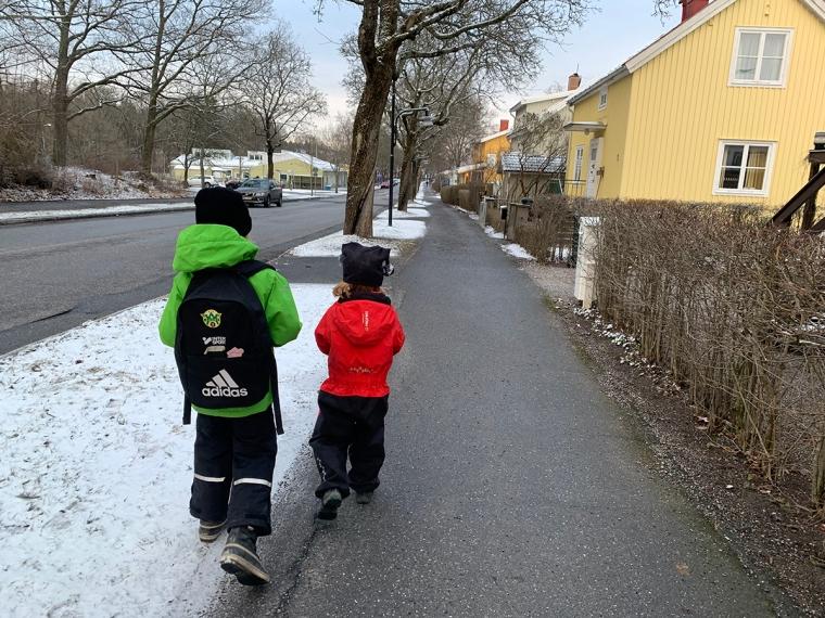 Två barn går på en väg med snö i kanten.