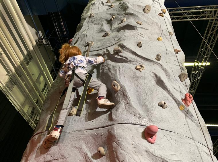 Ett barn klättrar på en klättervägg.