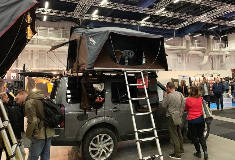 En bil med ett tält på taket.