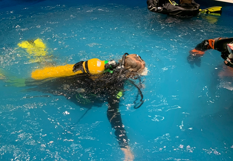 Ett barn dyker i en pool.