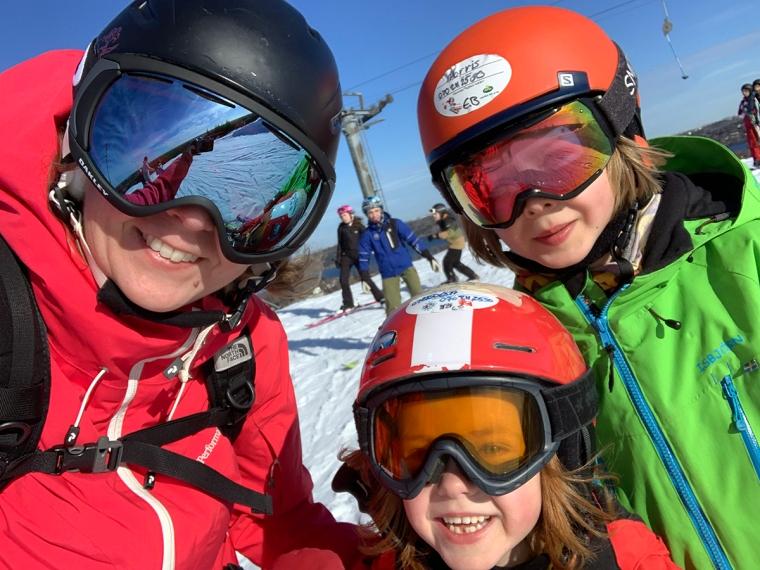 En vuxen och två barn med hjälmar och skidglasögon.