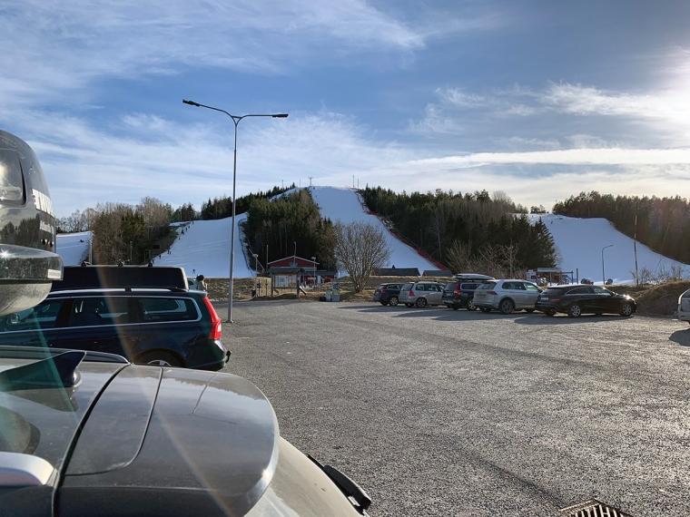 Bilparkering med 4 skidbackar i bakgrunden.