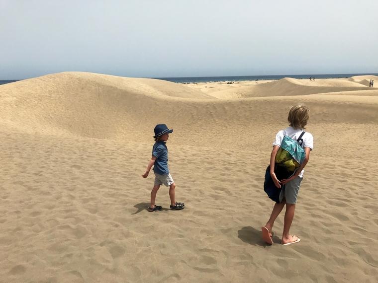 Två barn som går bland sanddyner, hav i bakgrunden.