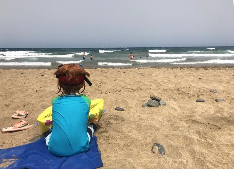 Ett barn sitter på en strand och blicker ut över vågorna i havet.
