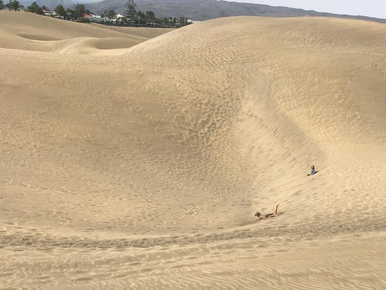 Två barn kastar sig i sanddynerna.