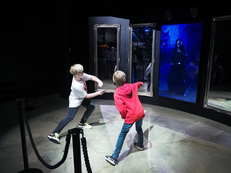 Två barn tränar med sina trollstavar.