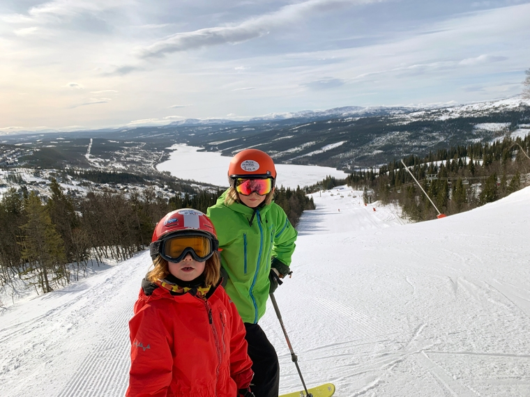 Två barn står övers i en slalombacke.