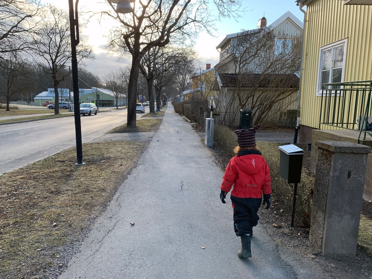 Ett barn går på en trottoar med vinteroverall.