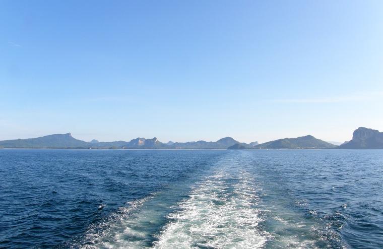 Bild tage från en båt med vågor och land i bakgrunden.