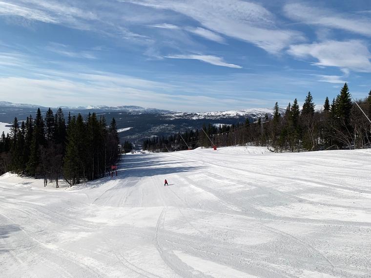 En tom slalombacken med ett litet barn på väg ner.