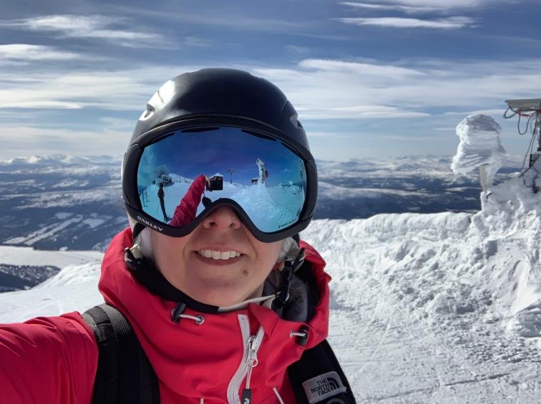 En kvinna tar en selfie med skidglasögon på. Berget speglar sig i skidglasögonen.