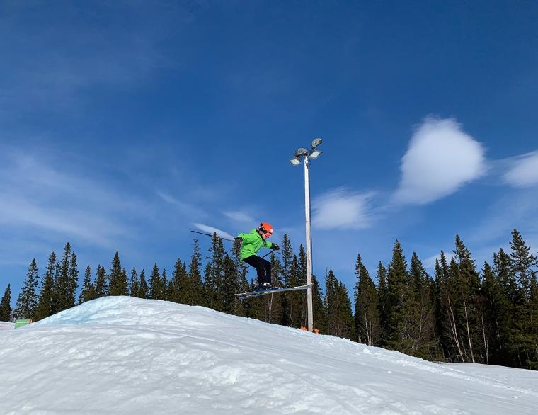 Ett barn som hoppar med skidor.