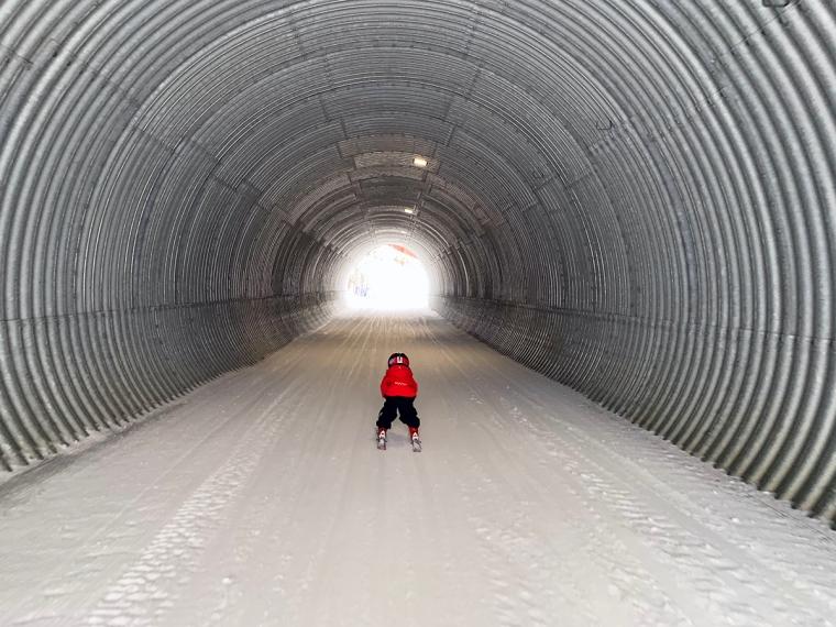 Ett barn åker bredbent på skidor genom en tunnel.