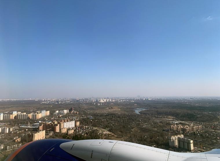 Bild fotad från flygplansfönster över en stad.