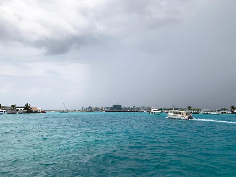 Turkost vatten med några vita båtar och en stad i bakgrunden.