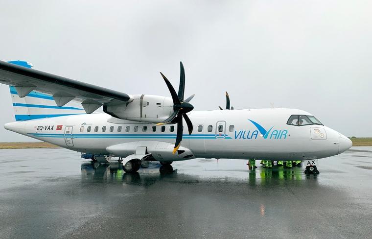 Ett vitt flygplan med blå text Villa Air.