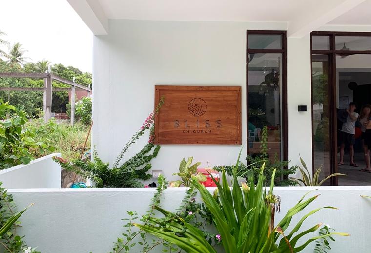 En bild på en entré till ett hotell. Vit byggnad med en skylt i trä med texten Bliss Dhigurag.