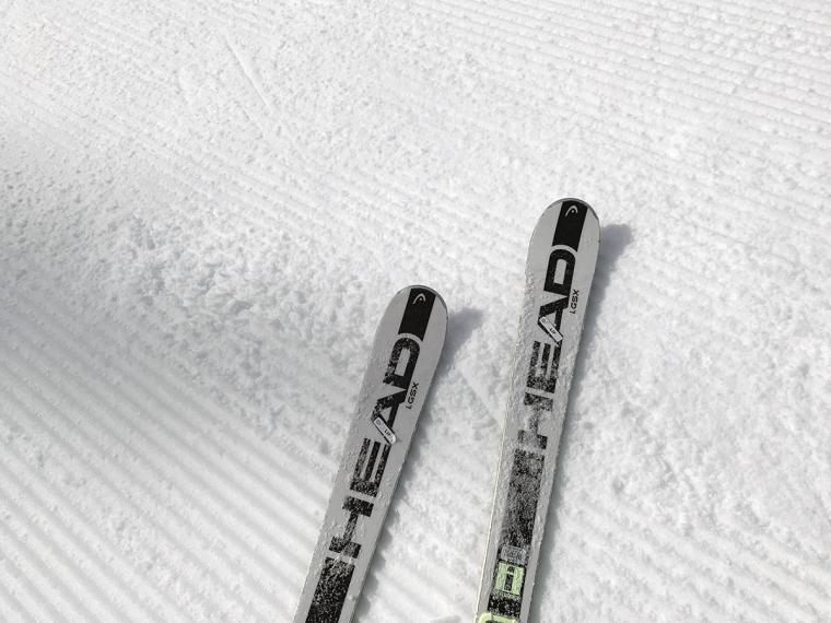 Två skidor på i en nypistad slalombacke.