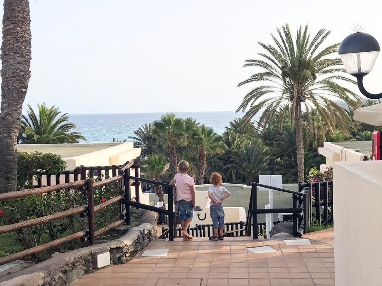 Två barn står övers på en trappa med havet i bakgrunden.