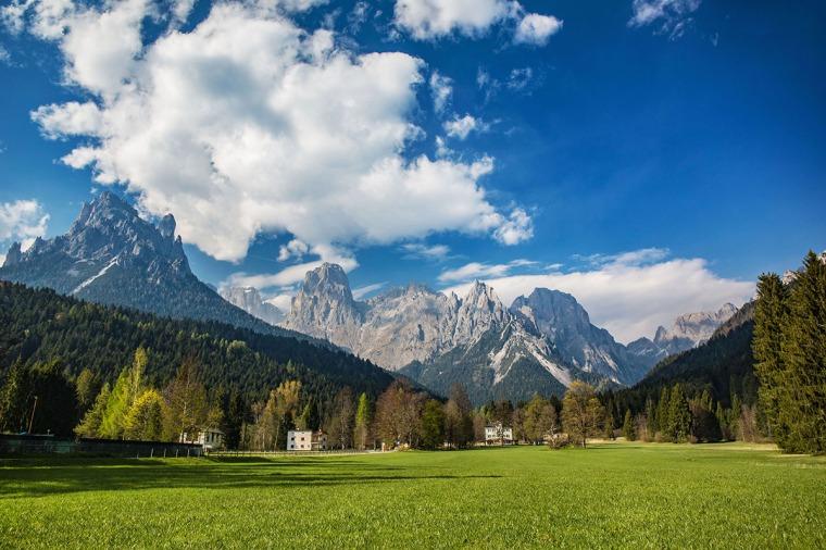 Grön äng i förgrunden och berg i bakgrunden.