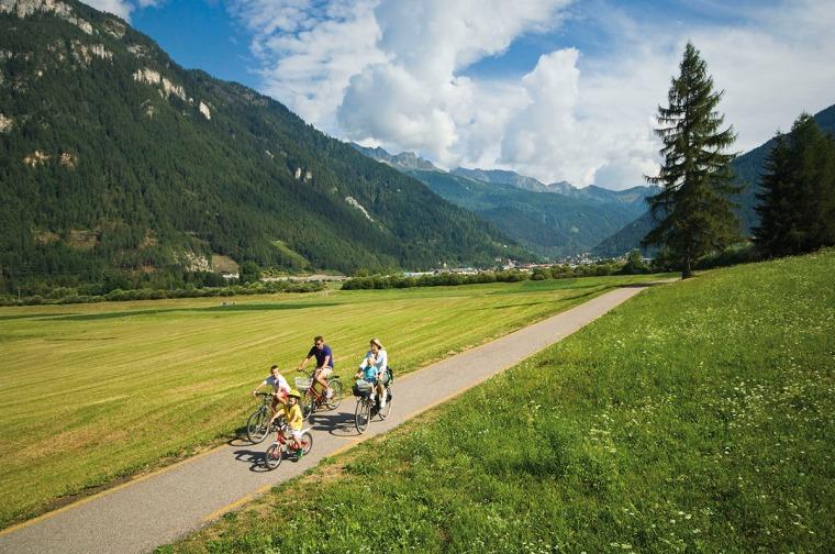 Berg i bakgrunden och en familj medc tre barn som cyklar på gen grusväg.