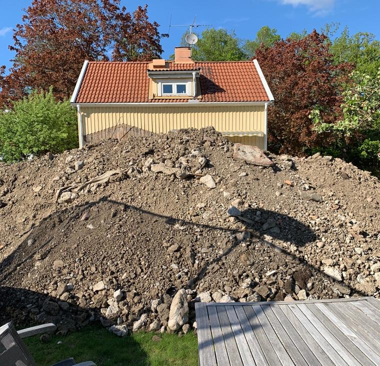 En stor jordhög där man skymtar ett gult hus bakom.