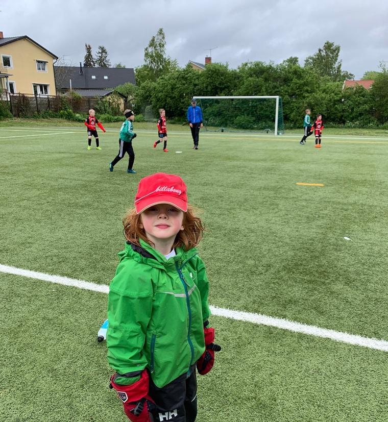 Ett barn som står vid linjen till en fotbollsplan där match pågår.