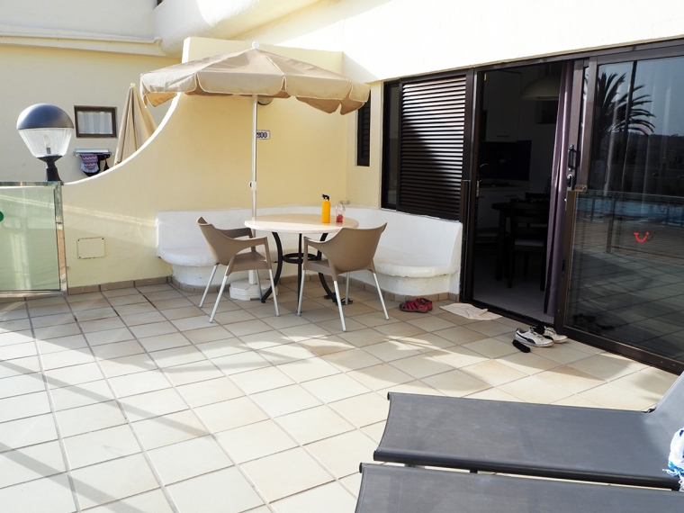 En bänk med ett runt bord och två stolar samt ett parasoll. i förgrunden syns två solbäddar.