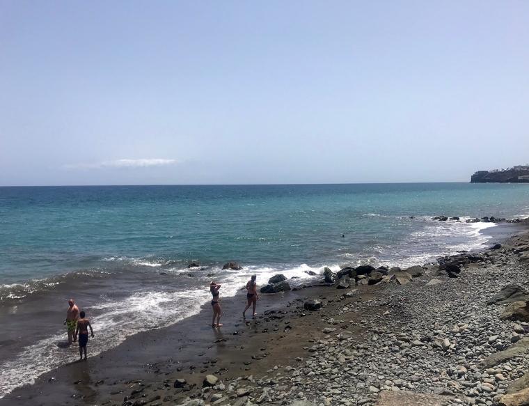 Stenig strand med ett par människor.