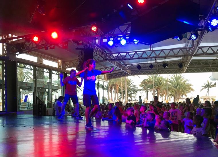 Två dansare på scenen och en hög ungar nedanför.