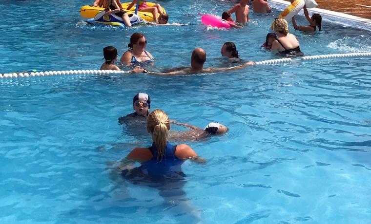 Två barn med simmösor och en simlärare i poolen.