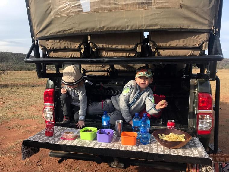 Två barn har klättrar in längst bak på en safaribil där det står snacks framdukat.