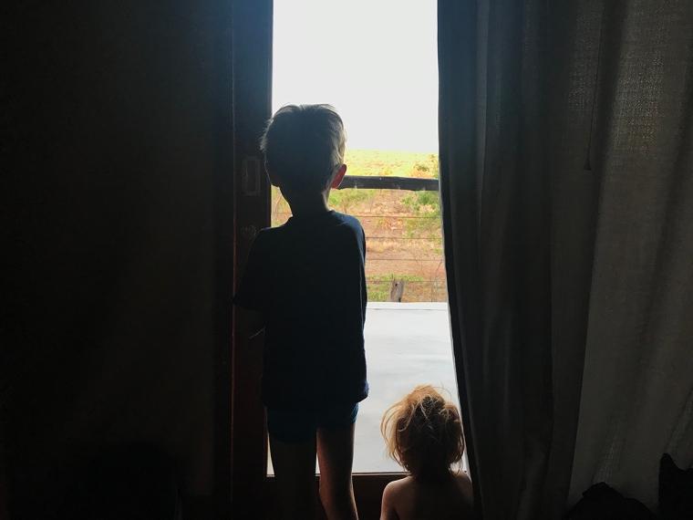 Två barn med ruffsigt hår tittat ut genom en glasdörr.
