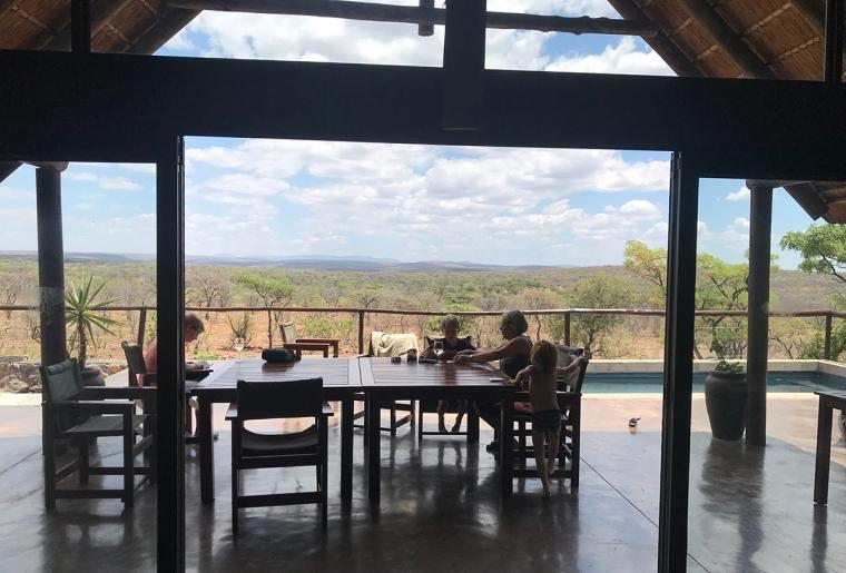 En vuxen och två barn spelar kort vid ett bord. I bakgrunden en savann.