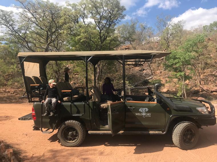 Tre barn klättrar på en öppen safaribil med plats för 10 personer och en chauför